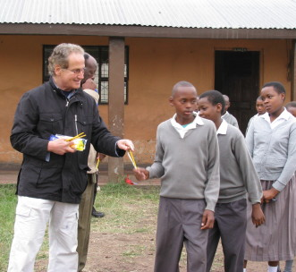 James Smith handing out school supplies to students in Sakila, Tanzania